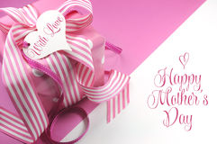 Beautiful pink gift on pink and white background with sample text and copy space for your text here for Mothers Day. International Womens Day, female birthday Stock Images