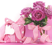 Beautiful pink gift and roses on pink and white background with copy space Stock Photo