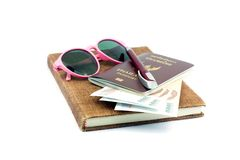 Beautiful pink glasses and Thailand passport with Thai cash on. Brown notebook on white background stock images