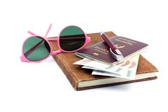 Beautiful pink glasses and Thailand passport with Thai cash on. Brown notebook on white background royalty free stock photos