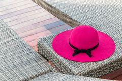 Beautiful pink hat with black bow on a pool chair stock photo