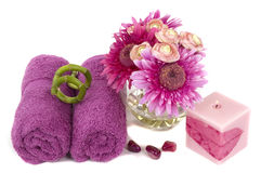 Beautiful pink-lilac daisies, candle, towels, and pebbles Royalty Free Stock Photography