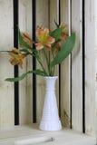 Beautiful pink lilies in white vase. Elegant and Beautiful pink lilies in white vase and wooden background Royalty Free Stock Image