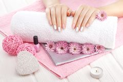 Beautiful pink manicure with chrysanthemum flower and towel on the white wooden table. spa Royalty Free Stock Photo