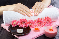 Beautiful pink manicure with chrysanthemum and towel on the black wooden table. spa Stock Photo