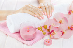Beautiful pink manicure with orchid, candle and towel on the white wooden table. Stock Photography