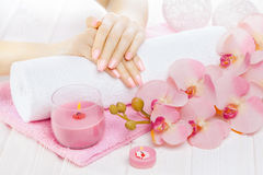 Beautiful pink manicure with orchid, candle and towel on the white wooden table. Royalty Free Stock Photos
