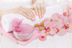 Beautiful pink manicure with orchid, candle and towel on the white wooden table. Stock Photos