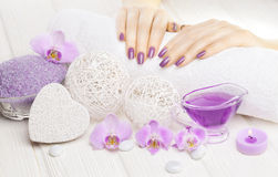 Beautiful pink manicure with orchid and towel on the white wooden table. spa Stock Photos