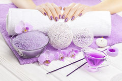 Beautiful pink manicure with orchid and towel on the white wooden table. spa Royalty Free Stock Photography