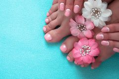 Beautiful pink manicure and pedicure with flowers. On a blue background royalty free stock photo