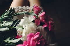 Beautiful pink peonies on legs of boho girl in white bohemian dress, top view. space for text. stylish hipster woman sitting with. Flowers in moody morning royalty free stock photography
