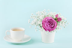 Beautiful pink rose flower and gypsophilla in vase and cup of coffee on turquoise vintage table for cozy breakfast. Royalty Free Stock Photo