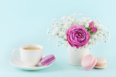 Beautiful pink rose flower and gypsophilla in vase, macaroon and cup of coffee on turquoise vintage table for cozy breakfast. Royalty Free Stock Photo