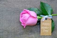 Beautiful pink rose with Happy Mother´s Day tag card on wooden background. Mothers Day festive concept with copy space. royalty free stock photos
