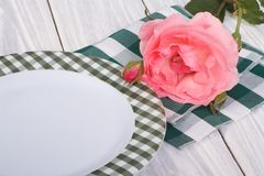 Beautiful pink rose and a plate on the table Royalty Free Stock Photos