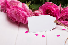 Beautiful pink roses and empty paper card on the white wooden ta Stock Photo