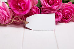 Beautiful pink roses and empty paper tag Royalty Free Stock Photography