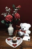 Beautiful pink roses in a vase accented with Baby`s Breath flowers, heart shaped white dollie with a decorated cup cake with a he stock photo