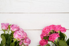 Beautiful pink roses with water drops on wooden surface Stock Photos