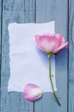 Beautiful, pink roses on wooden, rustic background with white paper Stock Photo