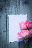 Beautiful, pink roses on wooden, rustic background with white paper and copy space Royalty Free Stock Images