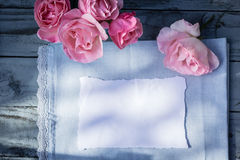 Beautiful, pink roses on wooden, rustic background with white paper and copy space Stock Photography