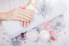 Beautiful pink and silver Christmas manicure with spa essentials. On wooden white background Royalty Free Stock Photo