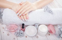 Beautiful pink and silver Christmas manicure with spa essentials. On wooden white background Royalty Free Stock Photography