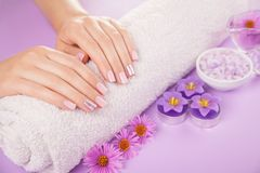 Beautiful pink and silver manicure with flowers and spa essentials. On purple background Stock Photo