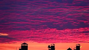 Beautiful pink sunset clouds move over town rooftops. Long shot Stock Photos