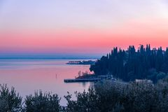 Beautiful pink sunset on Lake Garda. View of the embankment and piers of the city of Sirmione. Winter time on the lakes of Italy stock photo