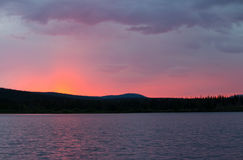 A beautiful pink sunset over a mountain lake. Royalty Free Stock Image