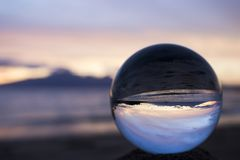 Beautiful Pink Sunset Seascape Captured in Glass Ball. Sunset with island in silhouette on horizon captured in glass ball on shore stock photo