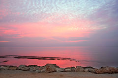 Beautiful pink sunset water background. Reflection of the sky in water Stock Photos