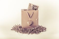 Beautiful pink surprise present bag with love symbol heart. Wonderful vintage gift with a card inside, maybe voucher or concert tickets for Valentine& x27;s Day Royalty Free Stock Photos