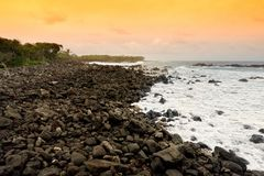 Beautiful pink tinted waves breaking on a rocky beach at sunrise on east coast of Big Island of Hawaii. USA Stock Image