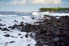 Beautiful pink tinted waves breaking on a rocky beach at sunrise on east coast of Big Island of Hawaii. USA Stock Images