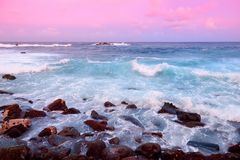Beautiful pink tinted waves breaking on a rocky beach at sunrise on east coast of Big Island of Hawaii. USA Stock Photo