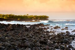 Beautiful pink tinted waves breaking on a rocky beach at sunrise on east coast of Big Island of Hawaii. USA Royalty Free Stock Images