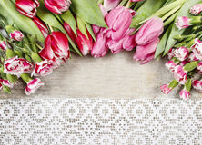 Beautiful pink tulips and carnations on wooden background Royalty Free Stock Image