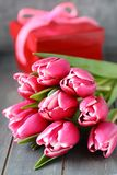Beautiful pink tulips with gift box on wooden background Stock Images