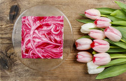 Beautiful pink and white tulips and pink cake Stock Image