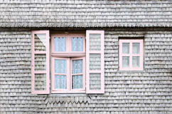Beautiful pink windows on facade of a wooden house Royalty Free Stock Image