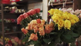 Beautiful pink and yellow roses are in a vase in a flower shop. Rose bouquets in a vase in a floral salon. Flowers are standing in water for saving freshness stock footage