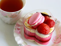 Beautiful pink yogurt cake decorate with macaron and strawberry and cup of tea Stock Photos