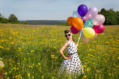 Beautiful pinup girl with balloon on a meadow Royalty Free Stock Photography