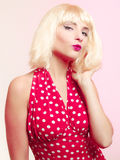 Beautiful pinup girl in blond wig and retro red dress blowing a kiss. Royalty Free Stock Photos