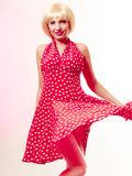 Beautiful pinup girl in blond wig and retro red dress dancing. Party. Stock Image
