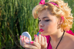 Beautiful pinup girl checking makeup Royalty Free Stock Photography
